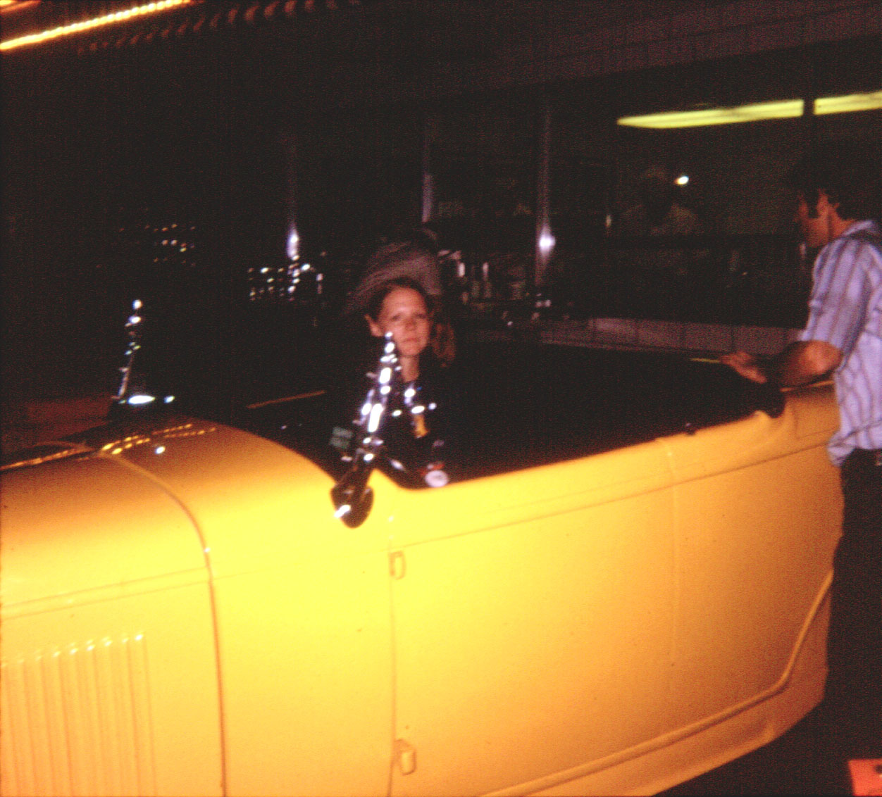 Maureen, sitting in Don's roadster
